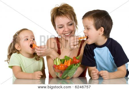 Woman Feeding Kids With Vegetables
