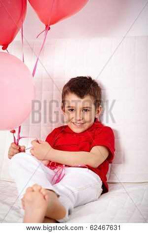 Portrait of happy lad with balloons relaxing on sofa