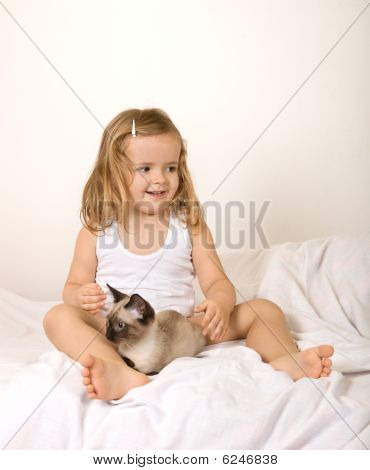 Little Girl Playing With Her Kitten In Bed