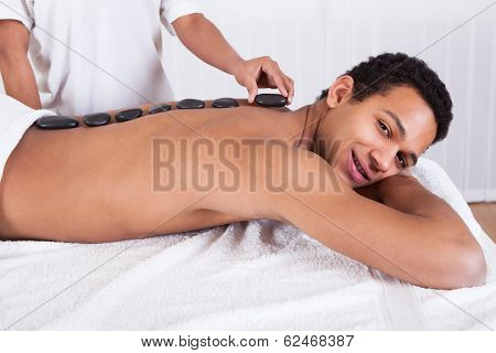Woman Placing Lastone On Man Back