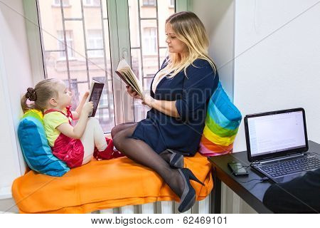 Pretty Daughter With Young Mother Read Books On Window Sill
