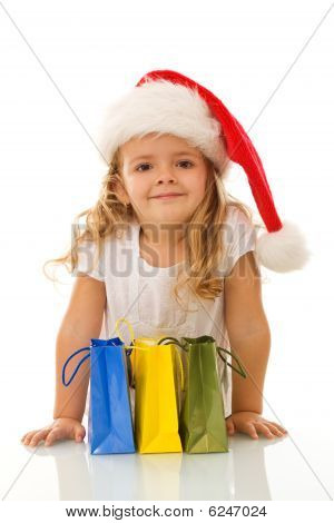Little Girl With Christmas Hat And Shopping Bags
