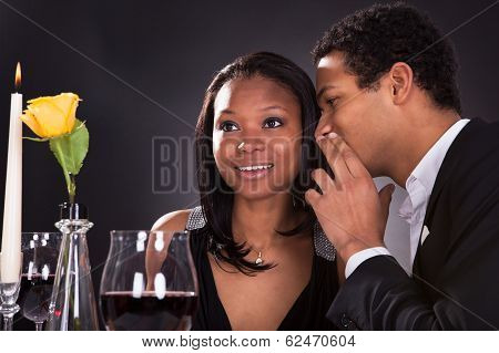 Man Whispering To Girlfriend's Ear