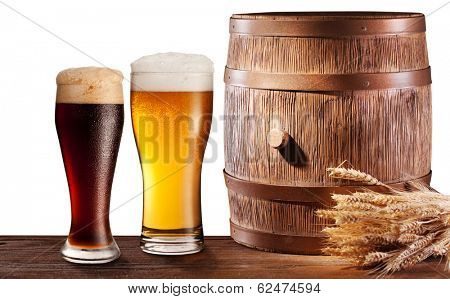 The glasses of beer near woden barrel. File contains clipping pathes.