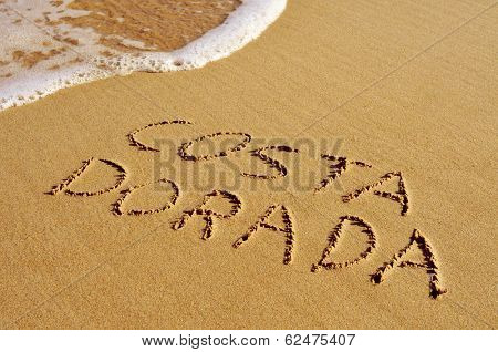 Costa Dorada, the name of an area of the Mediterranean coast of Spain, written in the sand of a beach