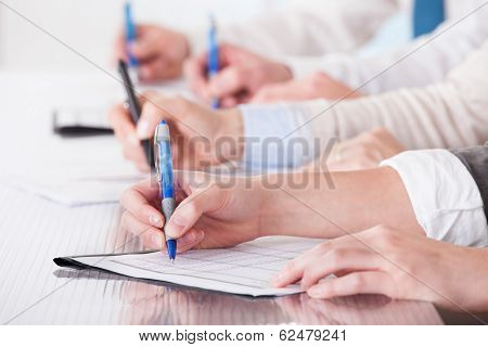 Business People Sitting In A Row And Writing Notes
