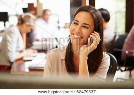Businesswoman Working At Desk Using Mobile Phone