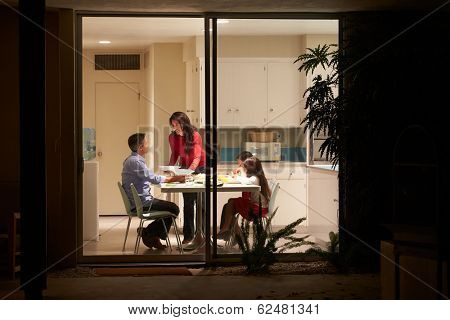 Family Eating Evening Meal Viewed From Outside