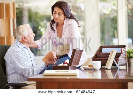 Senior Father Discussing Document With Adult Daughter