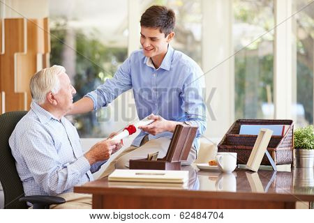 Grandfather Showing Document To Teenage Grandson