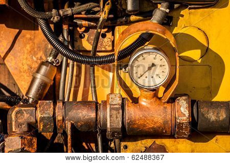 Close-up Of Dirty Hydraulic Machine With Pressure Clock. Horizontal Image.
