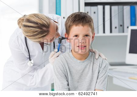 Portrait of boy being examined by female doctor with otoscope in clinic