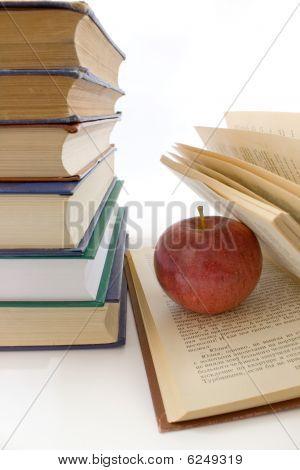 Manzana roja y pila de libros.