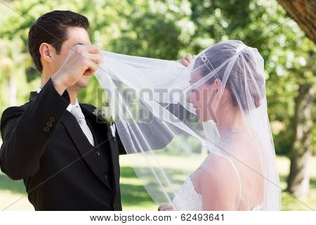 Young loving groom unveiling bride in garden
