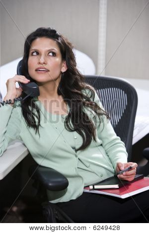 Hispanic female office worker sitting at cubicle desk on phone