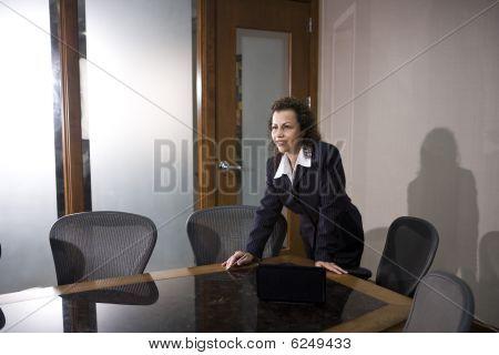 Hispanic businesswoman standing in a boardroom