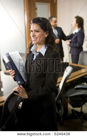 Confident Hispanic businesswoman in boardroom with colleagues