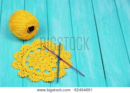 Yellow yarn for knitting with napkin and spokes on wooden table close-up
