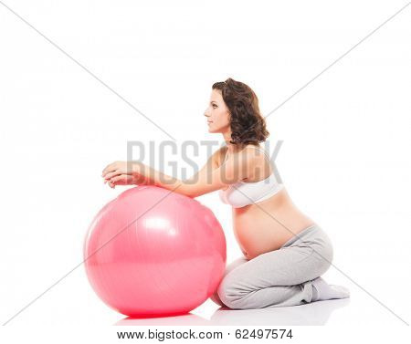 Young and healthy pregnant woman training with a fitness ball isolated on white