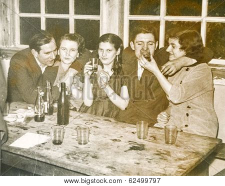 LODZ, POLAND, CIRCA 1950's: Vintage photo of young people parting and drinking alcohol together