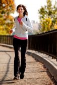 stock photo of workout-women  - A young woman jogging on a path in a park - JPG