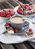 pic of eclairs  - Cup of coffee and chocolate eclairs with fresh berries - JPG