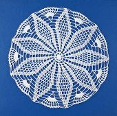 stock photo of doilies  - Handmade doily on blue background - JPG