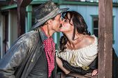 stock photo of outlaw  - Portrait of an old west woman and sheriff kissing - JPG