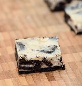 image of cheesecake  - Peace of cheesecake with oreo biscuit base on the wooden plate - JPG