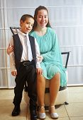 stock photo of sweet sixteen  - Young woman all dressed up in a teal dress for her Sweet Sixteen party with her brother in a vest and tie - JPG