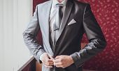 picture of boutonniere  - Hands of wedding groom getting ready in suit - JPG