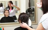 foto of hairspray  - Hairstylist with hairspray spraying hair of female client - JPG