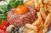 Tartar steak, raw meat steak with egg yolk, onion and french fries