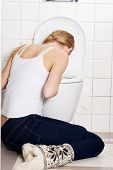 stock photo of vomiting  - Young caucasian woman is vomiting in the bathroom - JPG