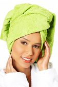 Portrait of attractive smiling woman wrapped in towel with turban. Closeup. Isolated on white.