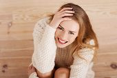 Picture of a careless young caucasian woman on the wooden floor wearing bright sweater.