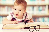 stock photo of librarian  - Happy funny baby girl in glasses reading a book in a library - JPG