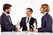 stock photo of congrats  - Image of three partners handshaking after negotiations with American - JPG