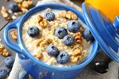stock photo of porridge  - Oatmeal with fresh blueberries over a rustic wooden background - JPG