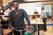 stock photo of commutator  - Architect Arrives At Work On Bike Pushing It Through Office - JPG