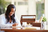 pic of person writing  - Woman Writing In Notebook Sitting At Desk - JPG