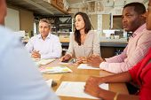 stock photo of pacific islander ethnicity  - Group Of Architects Sitting Around Table Having Meeting - JPG