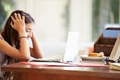 foto of 13 year old  - Stressed Teenage Girl Using Laptop On Desk At Home - JPG
