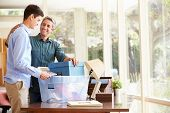 stock photo of packing  - Father Helping Teenage Son Pack For College - JPG