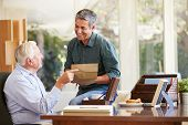 foto of keepsake  - Senior Father Discussing Document With Adult Son - JPG