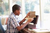stock photo of keepsake  - Boy Looking At Letter In Keepsake Box On Desk - JPG