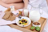 picture of bed breakfast  - Woman in bed with light breakfast - JPG