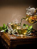foto of teapot  - vertical photo of the glass teapot flow green tea in cup on brown background tea ceremony - JPG