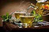 pic of teapot  - horizontal photo of the glass teapot flow green tea in cup on brown background tea ceremony - JPG