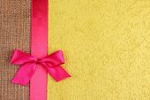 foto of sackcloth  - Sackcloth with color ribbon and bow on color paper background - JPG